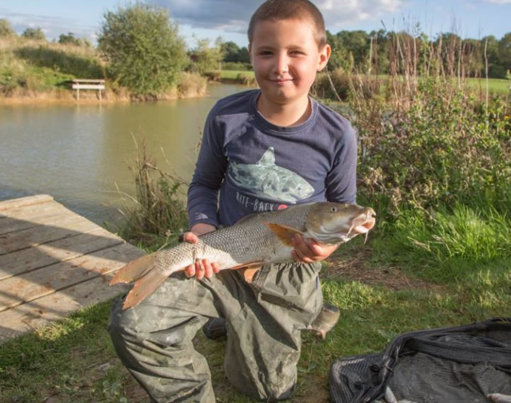 Cody with one of the lakes hard fighting stillwater barbel